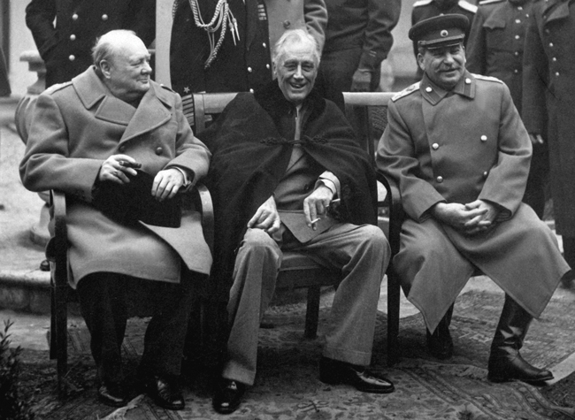 "Conference of the Big Three at Yalta makes final plans for the defeat of Germany. Here the ""Big Three"" sit on the patio together, Prime Minister Winston S. Churchill, President Franklin D. Roosevelt, and Premier Josef Stalin. February 1945."